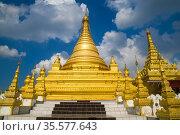 Одна из золотых ступ буддистского храма Kuthodaw Pagoda  на фоне облачного неба. Мандалай, Мьянма (Бирма) (2016 год). Стоковое фото, фотограф Виктор Карасев / Фотобанк Лори