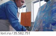 A chubby woman paint artist drawing an abstract blue painting with a palette knife. Стоковое видео, видеограф Константин Шишкин / Фотобанк Лори