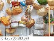 Eco-friendly products, a variety of natural straw wicker baskets hanging on the shop window on sale. Редакционное фото, фотограф Светлана Евграфова / Фотобанк Лори