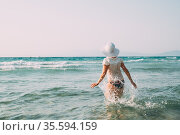 Young Caucasian Lady Woman In Swimsuit And Summer Hat Walking In Sea... Стоковое фото, фотограф Ryhor Bruyeu / easy Fotostock / Фотобанк Лори