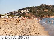 Adults and children rest on the Kleopatra beach. It is famous sandy beach close to mountain with the Alanya castle. The Mediterranean sea. Turkey. Редакционное фото, фотограф Кекяляйнен Андрей / Фотобанк Лори