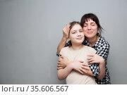 Woman in plaid shirt embracing her daughter. Стоковое фото, фотограф Дарья Филимонова / Фотобанк Лори