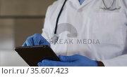 African american senior male doctor wearing white coat using digital tablet. Стоковое видео, агентство Wavebreak Media / Фотобанк Лори