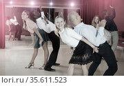 Glad smiling people practicing lindy hop technique in dance class. Стоковое фото, фотограф Яков Филимонов / Фотобанк Лори