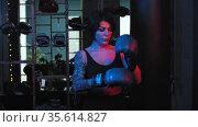 Tattooed woman puts on boxer gloves in neon lighting and standing in the fight pose. Стоковое видео, видеограф Константин Шишкин / Фотобанк Лори
