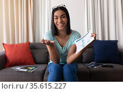 Mixed race gender fluid man working at home making video call holding documents and smiling. Стоковое фото, агентство Wavebreak Media / Фотобанк Лори