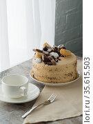 Сервированный к чаепитию стол: чайные чашки с блюдцами и бисквитный торт с масляным кремом, украшенный шоколадом и печеньем, на столешнице. Стоковое фото, фотограф Наталья Гармашева / Фотобанк Лори