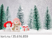 Two small cute snowmen friends with gifts in forest under falling snow. Стоковое фото, фотограф Zoonar.com/Ivan Mikhaylov / easy Fotostock / Фотобанк Лори