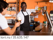Young man bartender giving beer with foam to man client. Стоковое фото, фотограф Яков Филимонов / Фотобанк Лори