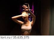 Beautiful girl in a white top covers her face with her palm from the light of the lamp. Стоковое фото, фотограф Женя Канашкин / Фотобанк Лори
