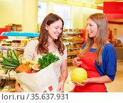 Lachende Verkäuferin zeigt Kundin eine Honigmelone. Стоковое фото, фотограф Zoonar.com/Robert Kneschke / age Fotostock / Фотобанк Лори