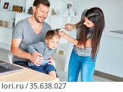 Mutter schneidet die Haare von ihrem Sohn mit Hilfe von Vater und... Стоковое фото, фотограф Zoonar.com/Robert Kneschke / age Fotostock / Фотобанк Лори