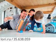 Kleinkind mit Koffer und aufblasbarem Rennauto spielt mit Eltern ... Стоковое фото, фотограф Zoonar.com/Robert Kneschke / age Fotostock / Фотобанк Лори