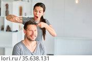 Junge Frau hat Spaß beim Haare schneiden von ihrem Partner mit Schere... Стоковое фото, фотограф Zoonar.com/Robert Kneschke / age Fotostock / Фотобанк Лори