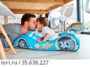 Vater gibt seinem Sohn einen Kuss im Kinderauto beim Spielen im Wohnzimmer. Стоковое фото, фотограф Zoonar.com/Robert Kneschke / age Fotostock / Фотобанк Лори