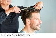 Frau beim Haare schneiden von einem Mann mit Schere beim Friseur. Стоковое фото, фотограф Zoonar.com/Robert Kneschke / age Fotostock / Фотобанк Лори