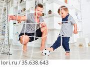 Vater spielt Fußball mit seinem Sohn im Wohnzimmer und zeigt ihm ... Стоковое фото, фотограф Zoonar.com/Robert Kneschke / age Fotostock / Фотобанк Лори