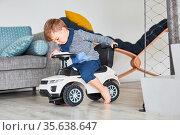 Kleiner Junge fährt mit einem Rutschauto oder Laufauto zu Hause im... Стоковое фото, фотограф Zoonar.com/Robert Kneschke / age Fotostock / Фотобанк Лори