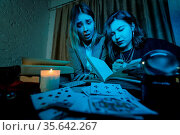Two women are reading a mysterious book, close view. Стоковое фото, фотограф Zoonar.com/Oleksii Hrecheniuk / easy Fotostock / Фотобанк Лори