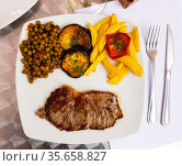 Fried veal tenderloin with fried potatoes, eggplant, peas and sauce. Стоковое фото, фотограф Яков Филимонов / Фотобанк Лори