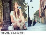 Woman sitting near lamp post drinking water. Стоковое фото, фотограф Яков Филимонов / Фотобанк Лори