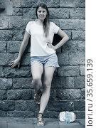 Young woman standing near old stone wall. Стоковое фото, фотограф Яков Филимонов / Фотобанк Лори