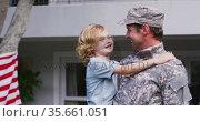 Caucasian military dad in uniform picking up his son in the garden. Стоковое видео, агентство Wavebreak Media / Фотобанк Лори