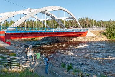 Люди рассматривают Лосевские пороги на реке Вуоксе рядом с арочным автомобильным мостом. Поселок Лосево Приозерского района Ленинградской области