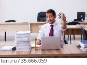 Young male employee holding moneybag in the office. Стоковое фото, фотограф Elnur / Фотобанк Лори