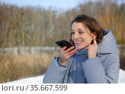 Lady in blue coat is sending audio voice message explaining something on smart phone at outdoor talking to mobile assistant. Girl using smartphone voice recognition and dictation. Стоковое фото, фотограф Ольга Балынская / Фотобанк Лори
