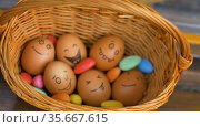 Stack of eggs with hand drawn faces on straw basket with colorful candy, easter preparation, holiday mood concepts. Стоковое видео, видеограф Ольга Балынская / Фотобанк Лори
