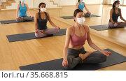 Group of attractive women in fase masks practice yoga lotus pose to meditation in modern studio. Стоковое видео, видеограф Яков Филимонов / Фотобанк Лори
