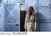 Portrait of young blonde female with long hair in beige cloak on metal wall background. Стоковое фото, фотограф Serg Zastavkin / Фотобанк Лори