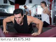 Man doing incline push-ups in gym. Стоковое фото, фотограф Яков Филимонов / Фотобанк Лори