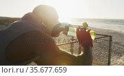 African american man drinking water, taking break in exercise outdoors by the sea. Стоковое видео, агентство Wavebreak Media / Фотобанк Лори