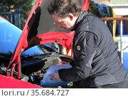 Neuenhagen, Germany, man fills antifreeze into windshield wiper system of his car. Редакционное фото, агентство Caro Photoagency / Фотобанк Лори
