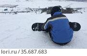 Сноубордист готовится к спуску по горнолыжному склону, поправляет крепления сноуборда. Редакционное видео, видеограф Кекяляйнен Андрей / Фотобанк Лори
