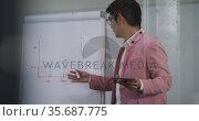 Asian businessman standing at whiteboard giving presentation using tablet gesturnig. Стоковое видео, агентство Wavebreak Media / Фотобанк Лори