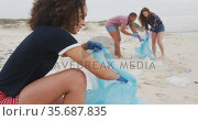 Diverse group of female friends wearing latex gloves collecting rubbish from the beach. Стоковое видео, агентство Wavebreak Media / Фотобанк Лори