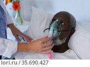 Female doctor putting oxygen mask ventilator on african american male patient lying in hospital bed. Стоковое фото, агентство Wavebreak Media / Фотобанк Лори
