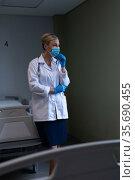Portrait of caucasian female doctor wearing mask and latex gloves looking ahead. Стоковое фото, агентство Wavebreak Media / Фотобанк Лори