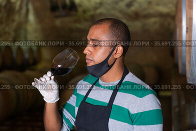 Positive sommelier in protective mask tasting red wine from barrels