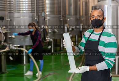 Man in protective mask with beaker in winery shop