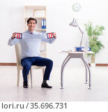 Man exercising with elastic band in office during lunch break. Стоковое фото, фотограф Elnur / Фотобанк Лори