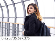 Young beautiful woman looks back walking along the covered overpass. Стоковое фото, фотограф Евгений Харитонов / Фотобанк Лори