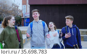 Group of smiling teen pupils chatting after lessons outdoors at warm spring day. Стоковое видео, видеограф Яков Филимонов / Фотобанк Лори