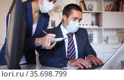 Portrait of young business woman focused on work with male colleague in office. People wearing medical face masks to prevent spread of viral infection. Стоковое видео, видеограф Яков Филимонов / Фотобанк Лори