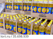 Russia, Samara, February 2021: Bottles of Golden Seed sunflower oil stand in crates, ready for sale in a large supermarket. Text in Russian: Golden Seed, First Grade, Vitamin E, Non-GMO. Редакционное фото, фотограф Акиньшин Владимир / Фотобанк Лори