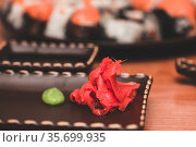 Red pickled ginger and vassabi on a brown clay plate. Japanese traditional food rolls. Стоковое фото, фотограф katalinks / Фотобанк Лори