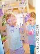 Kinder malen mit Fingerfarbe im Kindergarten ihre Hände an eine Glasscheibe. Стоковое фото, фотограф Zoonar.com/Robert Kneschke / age Fotostock / Фотобанк Лори